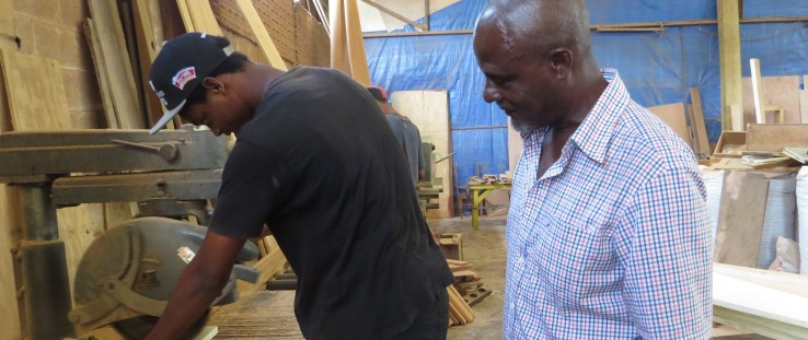 Tre Espirit uses the USAID-funded radial arm saw under the watchful gaze of his teacher, master craftsman John Riviere.