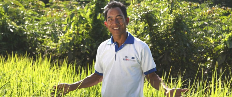 Kverk Sarak stands in his family's rice field on community titled land.