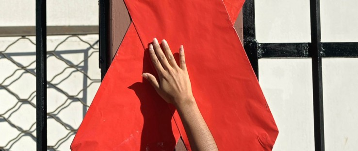 An activist sets up a red ribbon during the commemoration of the World AIDS Day in San Salvador.