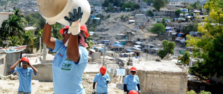 A woman catches a bucket in a line for rubble removal in the hilly Ravine Pintade neighborhood in Port-au-Prince, Haiti, Feb. 16