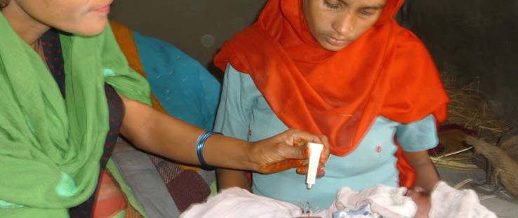 A community health volunteer applies chlorhexidine to the umbilical cord of a newborn delivered at home in Banke district.