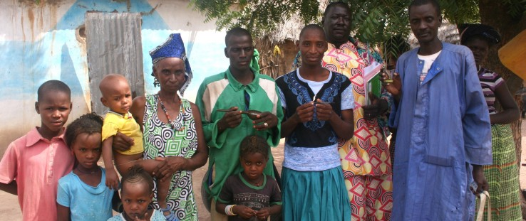 Rougui Diallo's family poses for a photo with two community health workers, at right, after a home visit.