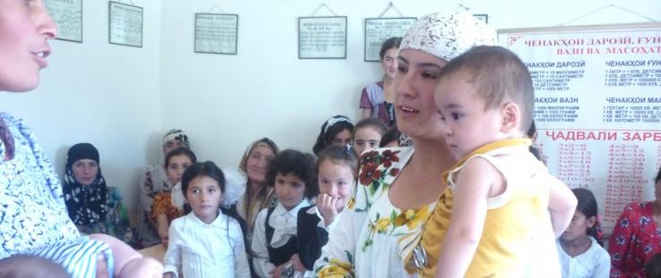 Children watch as women celebrate Breastfeeding Day in Hissor, Tajikistan.