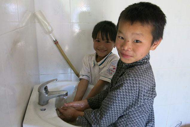 Two children wash their hands in a bathroom sink