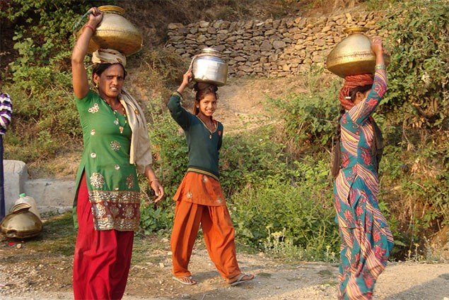 Village women carry water on their heads