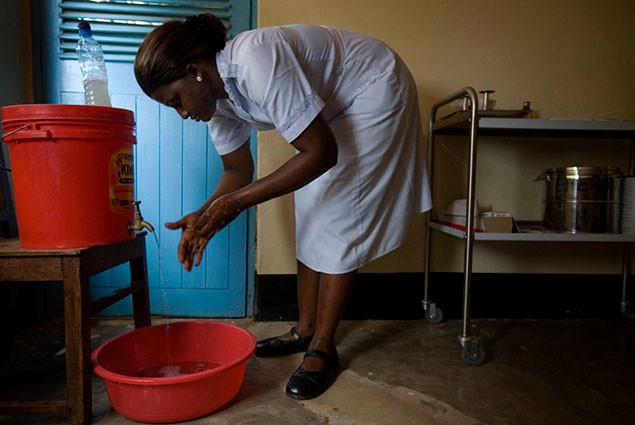 A nurses washes her hands over a washtub