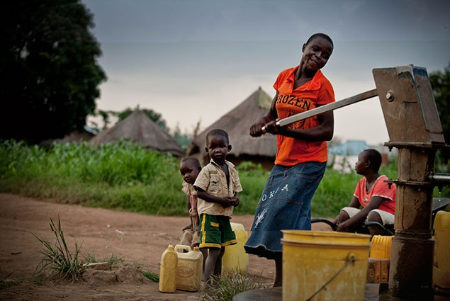 A young woman pumps water from a well