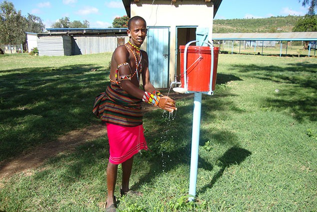 A Maasai man washes his hands from a suspended buicket of water