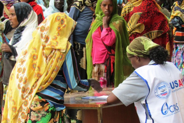USAID works with a number of non-governmental organization partners to support the Productive Safety Net Program in Ethiopia. Here a worker for USAID-partner Catholic Relief Services helps to organize distributions.