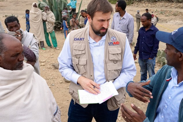 USAID Office of Foreign Disaster Assistance Director Jeremy Konydnyk discusses how Ethiopia's drought is affecting residents in the Enderta Woreda of Tigray Region. A Catholic Relief Services representative (right) is explaining how the current well rehabilitation will help alleviate the suffering by community members.
