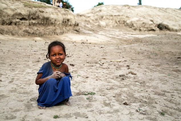 This little girl sits at the bottom of a basin that used to be a watering hole for an entire community of about 30 families. Her hands and feet are covered with a thin film of powdery gray silt, just like all the village children. There's no water to even wash it off.