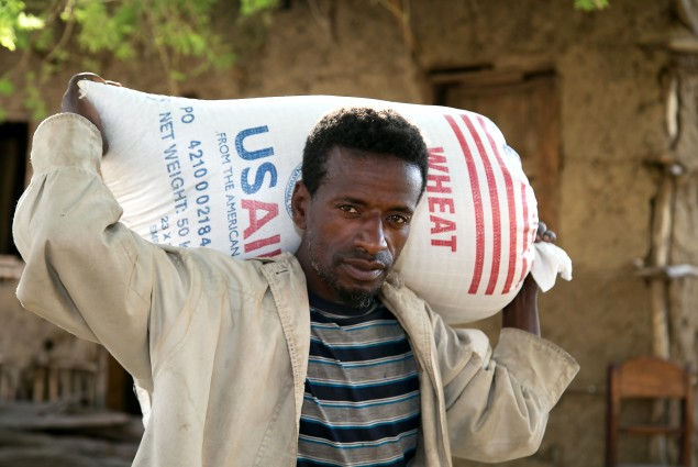This man in Aje, Ethiopia carries home his family's wheat ration.