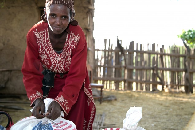 A woman prepares a food ration sack for the trip home.