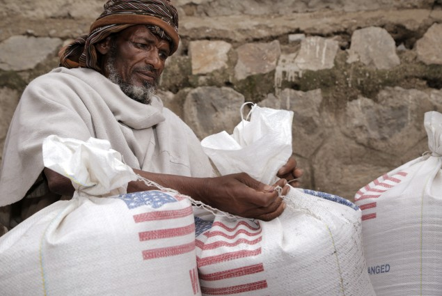 In Aje, a man ties his family's ration bags tightly to make sure nothing will be spilled on the journey home.