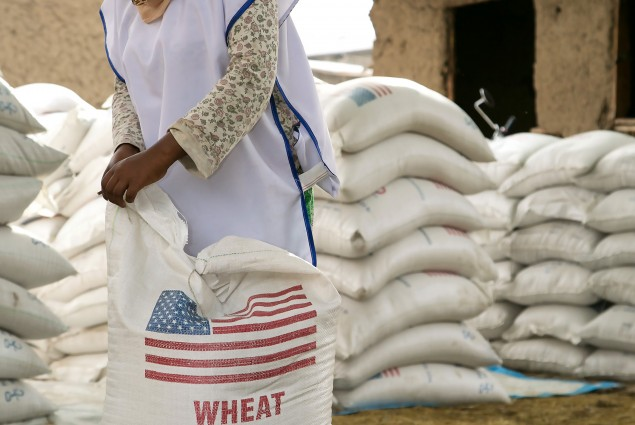 In Aje, families gather to take home rations of wheat and split yellow peas under the program, implemented by a number of national and international partners working under CRS' management.