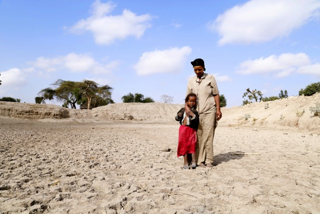 Badoo Fukura and one of her daughters stand at the bottom of a basin that used to be their community watering hole.