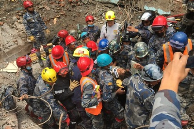 Members of a USAID DART help pull 15-year-old Pemba Tamang from rubble five days after a M7.8 earthquake in Nepal.