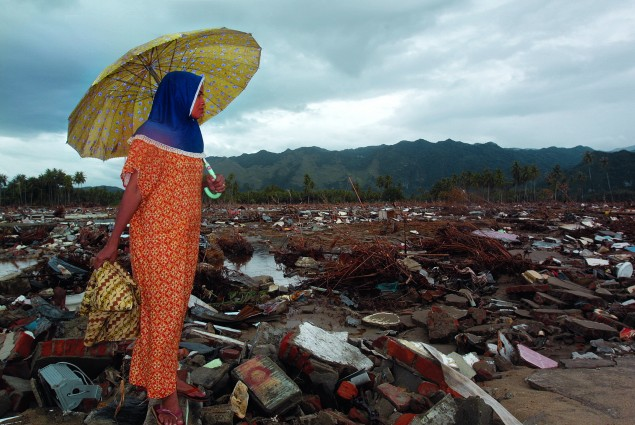 An Indonesian woman takes in the damage one day after a magnitude 9.0 earthquake produced deadly tsunami