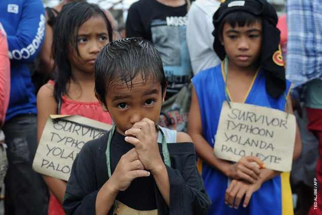 Survivors of the super Typhoon Haiyan, wait for a C-130 military plane at Tacloban airport, Leyte province, central Philippines,