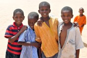A small group of young boys in Senegal smile at the camera