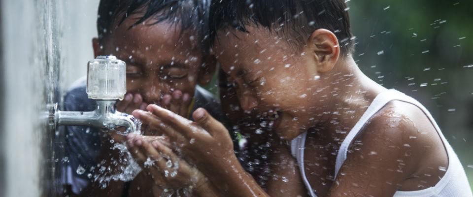 Children happily splash water to cool down.