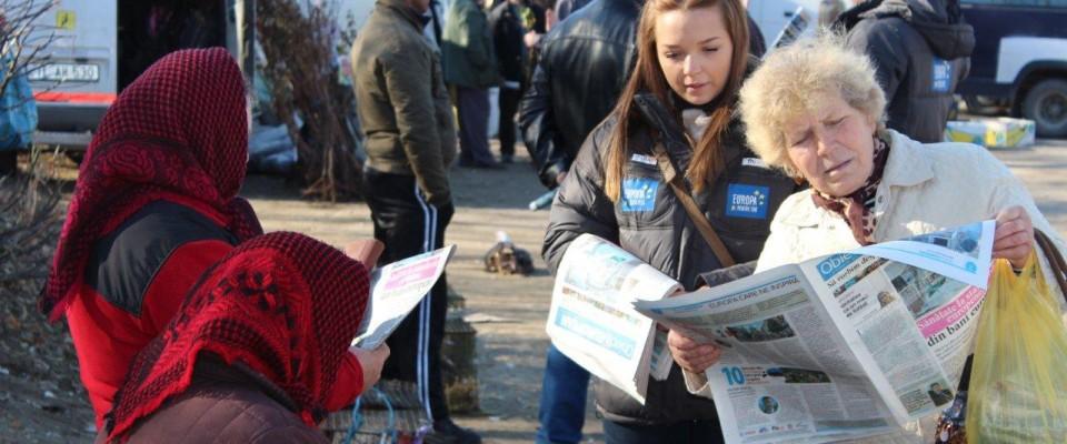 Un voluntar oferă locuitorilor unui sat din Moldova suplimentul de ziar despre integrarea europeană. USAID susține eforturile so