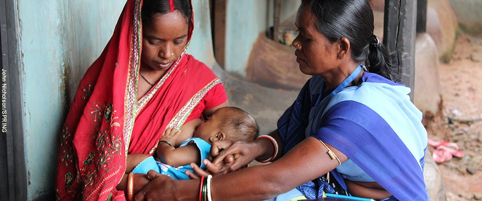 A health worker helps a new mother nurse her baby.