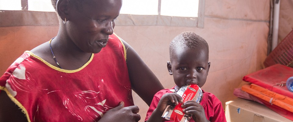 A mother is giving her malnourished baby ready-to-use therapeutic food from a packet.