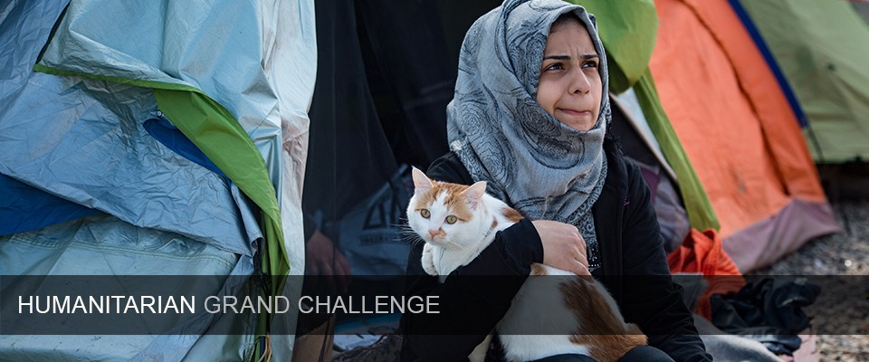 A girl holds Taboush, a cat travelling with a migrant family from war-torn Syria to Europe, in front of a tent in a makeshift camp at the Greek-Macedonian border near the village of Idomeni on March 21, 2016.  Greece will not be able to start sending refugees back to Turkey from March 20, 2016, the government said, as the country struggles to implement a key deal aimed at easing Europe's migrant crisis. The numbers are daunting: officials said as of Saturday there were 47,500 migrants in Greece, including 8