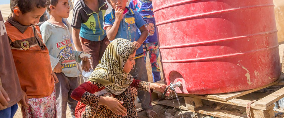 Fatima, 10, washes her face at a water tank provided by UNICEF in Tinah Camp on September 5, 2016. USAID has been supporting UNI