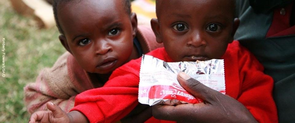 Two children eat from a meal packet.