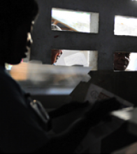 A poll worker reads out vote results on March 20, 2011, in Port-au-Prince as people peer through nearby windows. USAID assisted