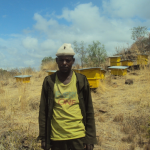 In the Amhara region of Ethiopia, Mariye Amsalu stands in front of the bee colonies his youth group manages.