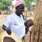 Mbene Dionne, with one of her own children, serves more than 1,000 people in four villages in Senegal.