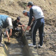 Young men from Zulpuev municipality clear the irrigation canal so thousands of farmers can receive water to maintain their crop