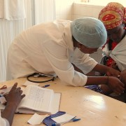 A nurse checks a child in Angola before prescribing antimalarial drugs.