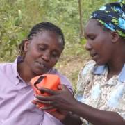 Kenyan women discuss the S300 mobile charging solar lantern.