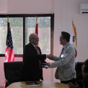 Handshakes are exchanged during the MOU signing ceremony