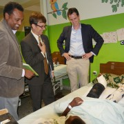 Chargé d'Affaires Peter Vrooman and hospital staff talk with a patient.