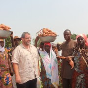 Andy Karas, Mission Director, with women carrying Orange flesh sweet potato