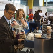 U.S. Chargé d'affaires to Ethiopia Peter Vrooman tries his hand as a barista at the 7th Africa Barista Championship & All Star Challenge booth. The booth is sponsored by USAID's East Africa Trade and Investment Hub.
